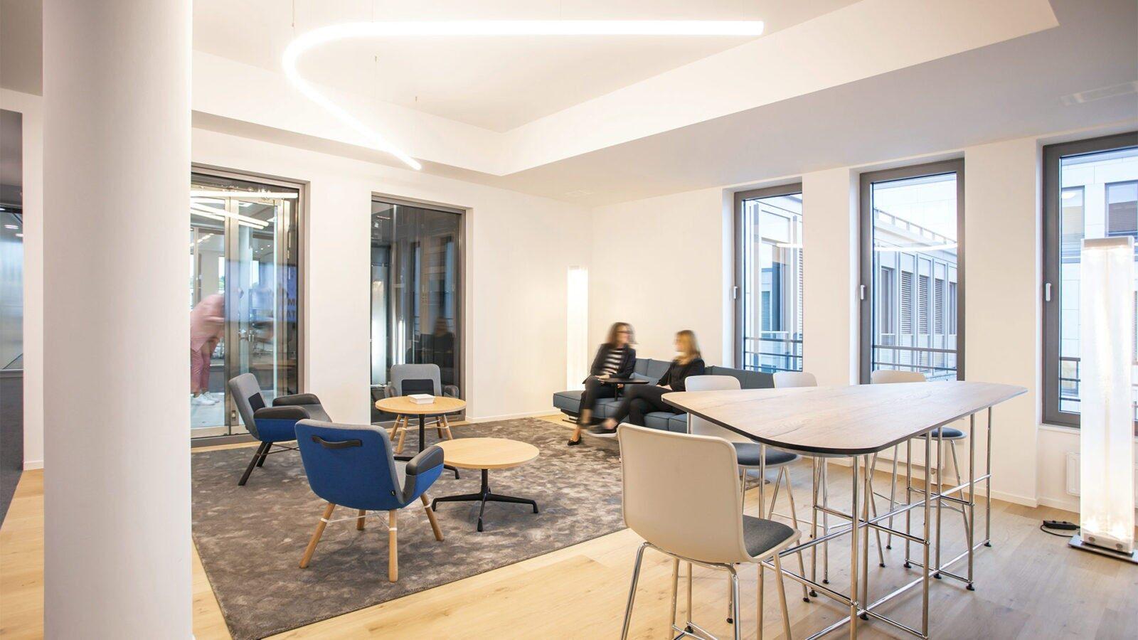 Büroeinrichtung mit Konzept: Lounge Bereich mit bequemen Sesseln, Sofa und Stehtisch für spontane Besprechungen