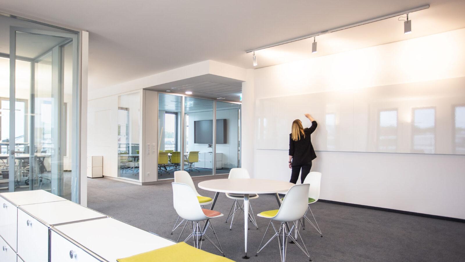 Vielseitig nutzbare Bürofläche mit kleinem Besprechungtisch und großem Whiteboard für kreative Zusammenarbeit im Team