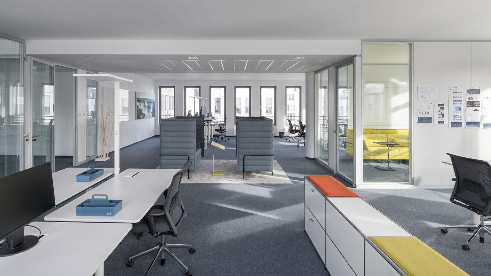 Tageslicht und offene Atmosphäre prägen die Büroeinrichtung mit Klarheit und frischen Farbakzenten